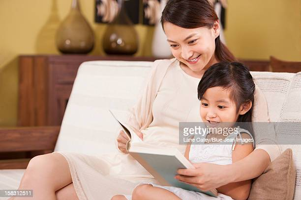 Little girl reading a book with mother