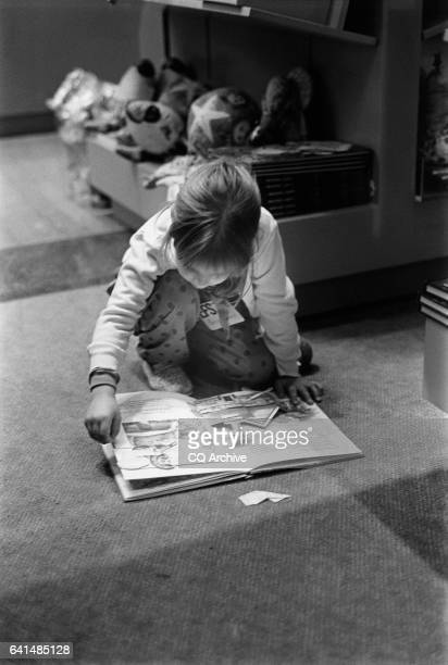 Little girl reading a popup book on the floor of the Library of Congress gift store April 22 1992