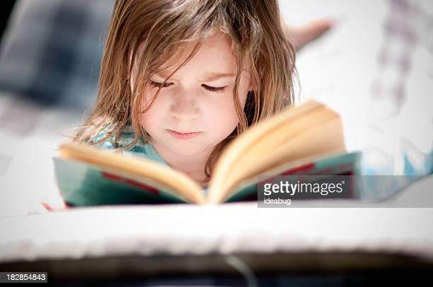 Rapariga ler um livro na cama de Fora