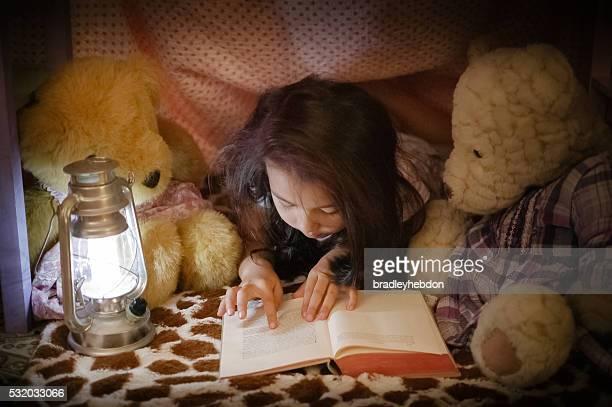 Fillette lisant un livre sur les ours en peluche de fort
