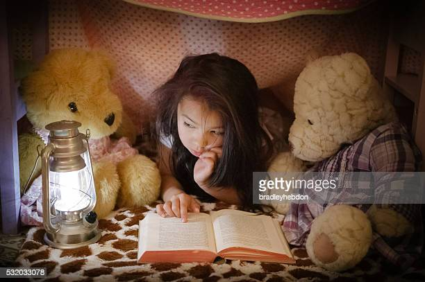 Little girl reading book to teddy bears in fort