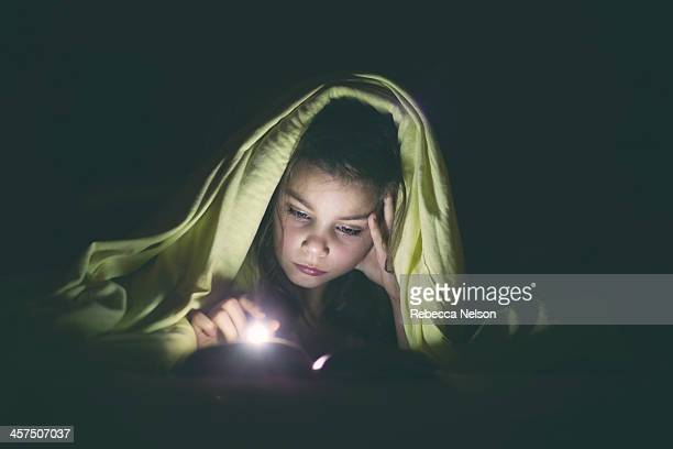 Little girl reading by flashlight