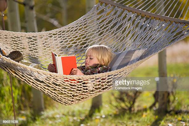 little girl reading in hammock