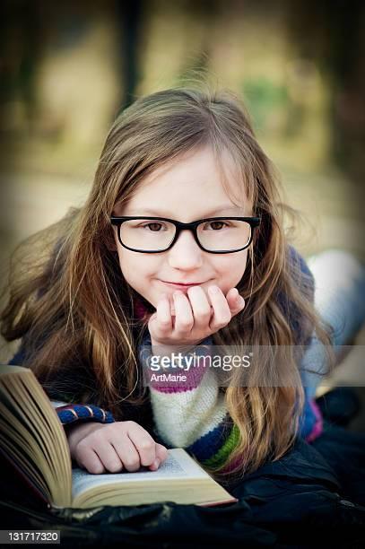 Fillette lisant dans le parc