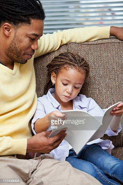 Little girl reading with father