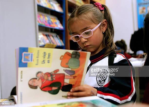 A little girl reads a book during the XXI Book Fair of Bogota on April 24 2008 AFP PHOTO/Mauricio DUEAS