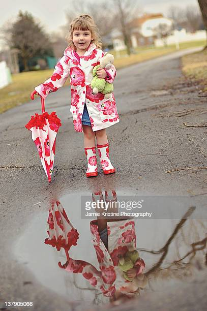 Little girl reflection in puddle