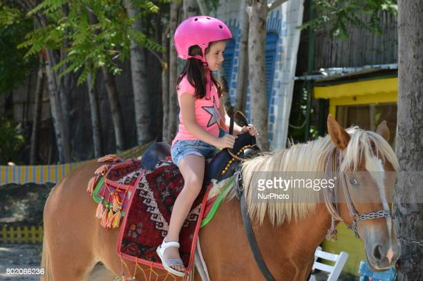 A little girl rides a horse at Cheerful Village in Ankara Turkey on June 27 2017 Mostly families and children visit the village to enjoy the holiday...