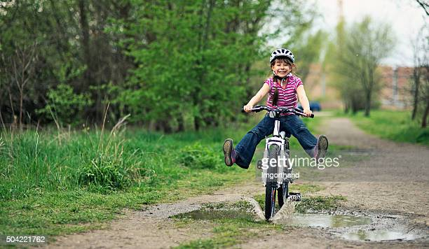 Little girl riding a bike  through a puddle.