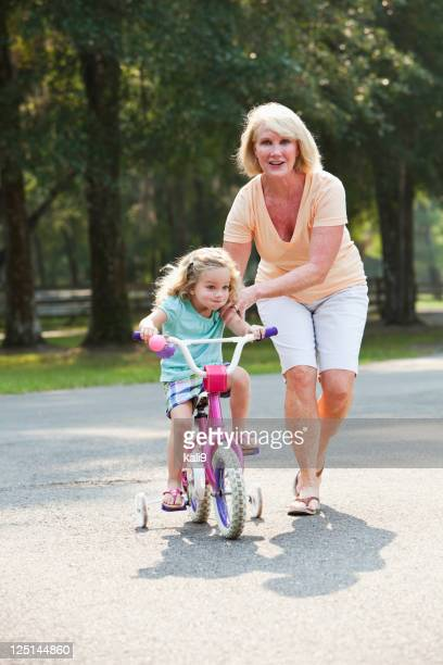 Little girl riding bike with grandmother