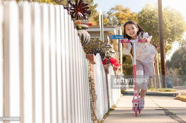 Little girl riding Ihrem Motorroller neben dem Bürgersteig