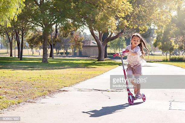 Petite fille équitation son scooter dans le parc