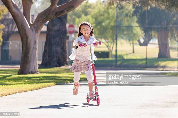 Little girl riding her scooter in the park