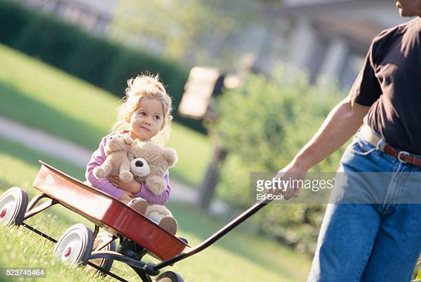 Little Girl Riding in Toy Wagon