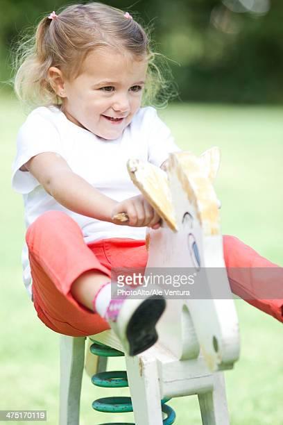Little girl riding rocking horse, portrait