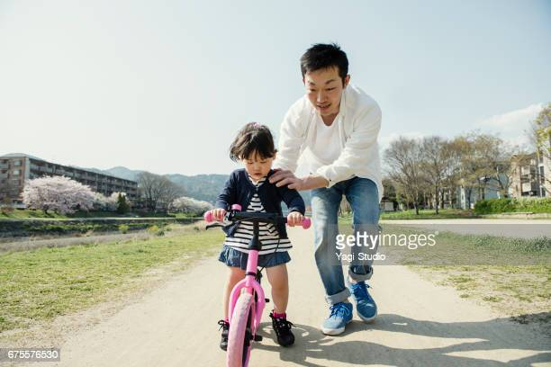 Little girl riding runbike with father