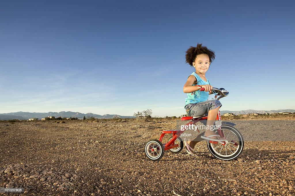 Little girl riding tricycle in Nevada desert