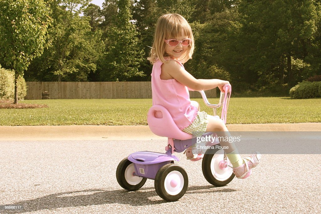 Little Girl Riding Tricycle on Street