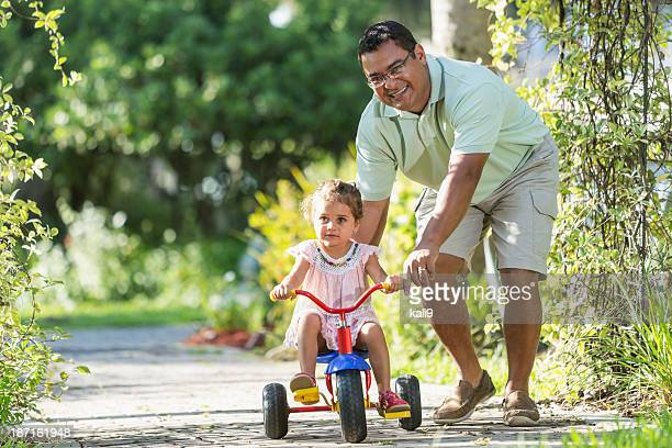 Little girl riding tricycle with daddy