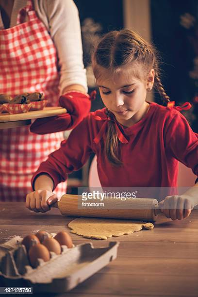 Little girl rolling dough