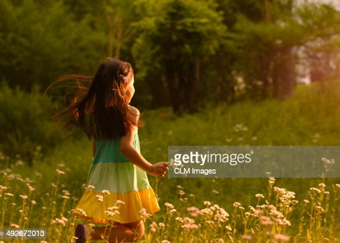 Little Girl Running In A Field Of Flowers Stock Photo ...