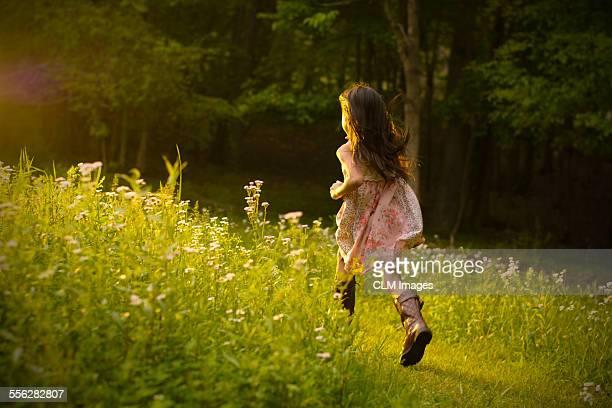 Little girl running in a field of flowers.