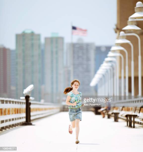 Little girl running on a pier towards the camera.