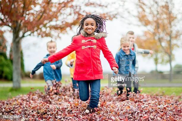 Petite fille courir à travers une feuille Pile