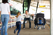 excited little girl running to her father at airport after a long wait with mother
