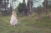 Little girl running with lantern