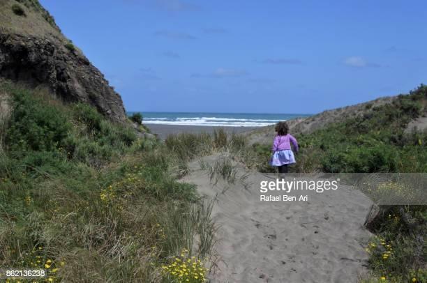 Little girl runs on a sand dune path