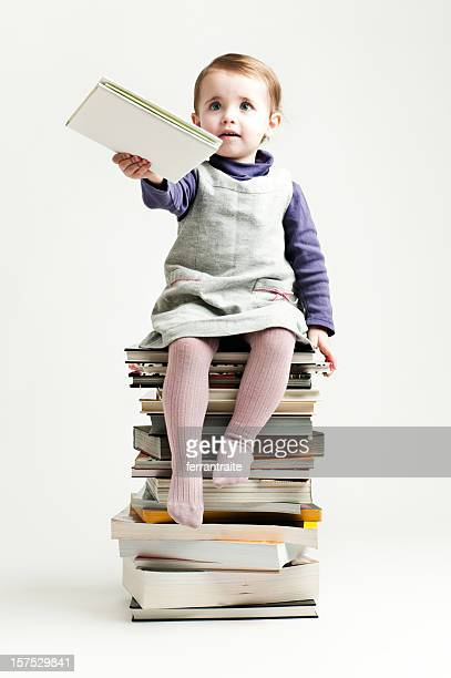 Little girl seated on a pile of books handing one