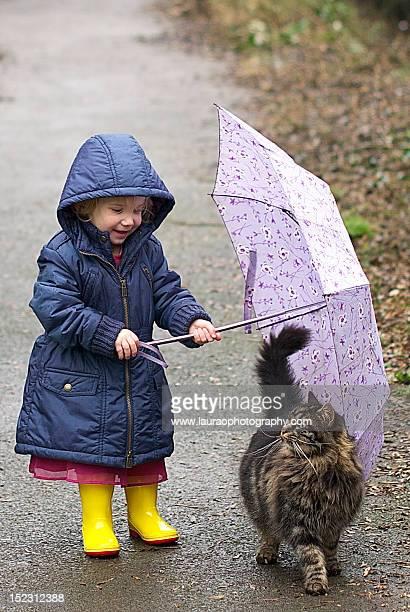 Little girl sheltering cat under umbrella