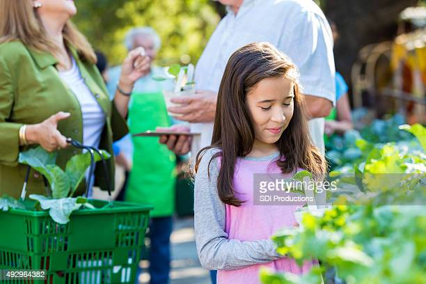 Little girl shopping at gardening store with mother