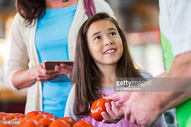Little girl shopping for produce in grocery store with mom