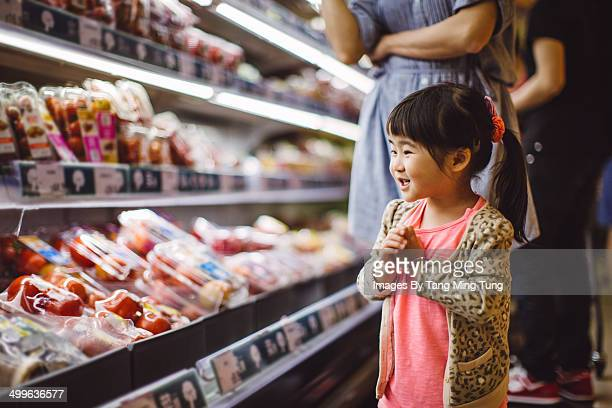 Little girl shopping in supermarket with mom