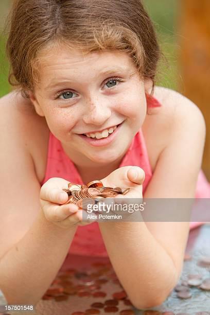Kleines Mädchen zeigen Münzen in den Händen