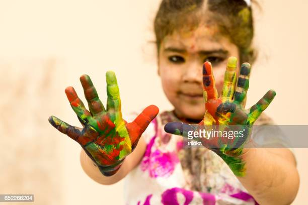 Little girl showing colorful painted hands