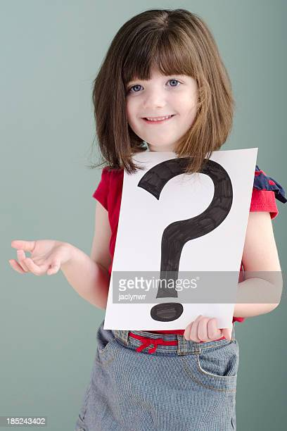 little girl shrugs while holding a question mark
