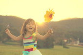 Little girl singing and dancing with toy windmill.