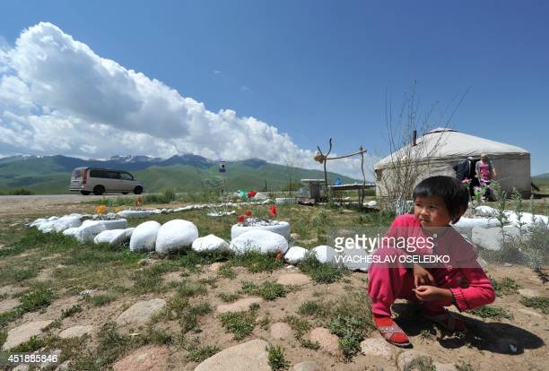 A little girl sits near a yurt the traditional portable dwelling on nomads at the SuuSamyr plateau500 meters above the sea level near the ancient...