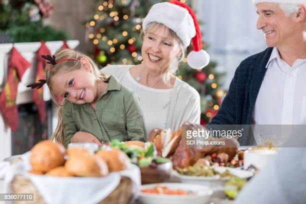 Meisje zit met grootouders tijdens het kerstdiner