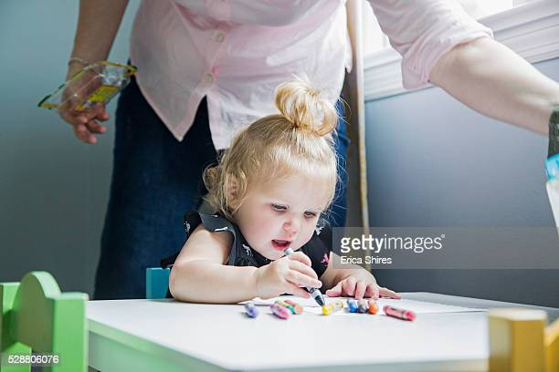 Little girl (12-23 months) sitting and drawing