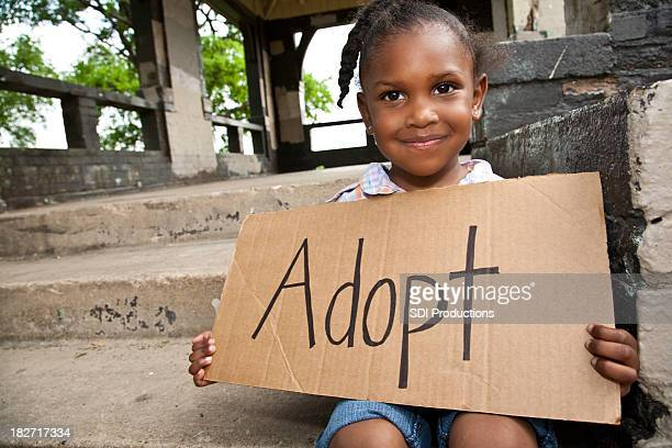 Little Girl Sitting and Holding Cardboard Sign Saying Adopt