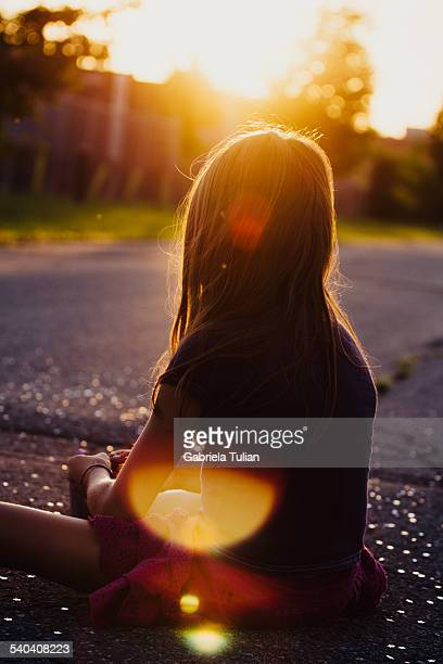 Little girl sitting appreciating the sunset