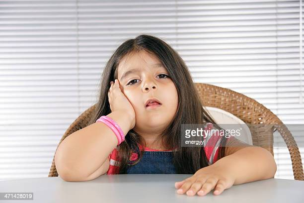 Little girl sitting at a table, looking bored
