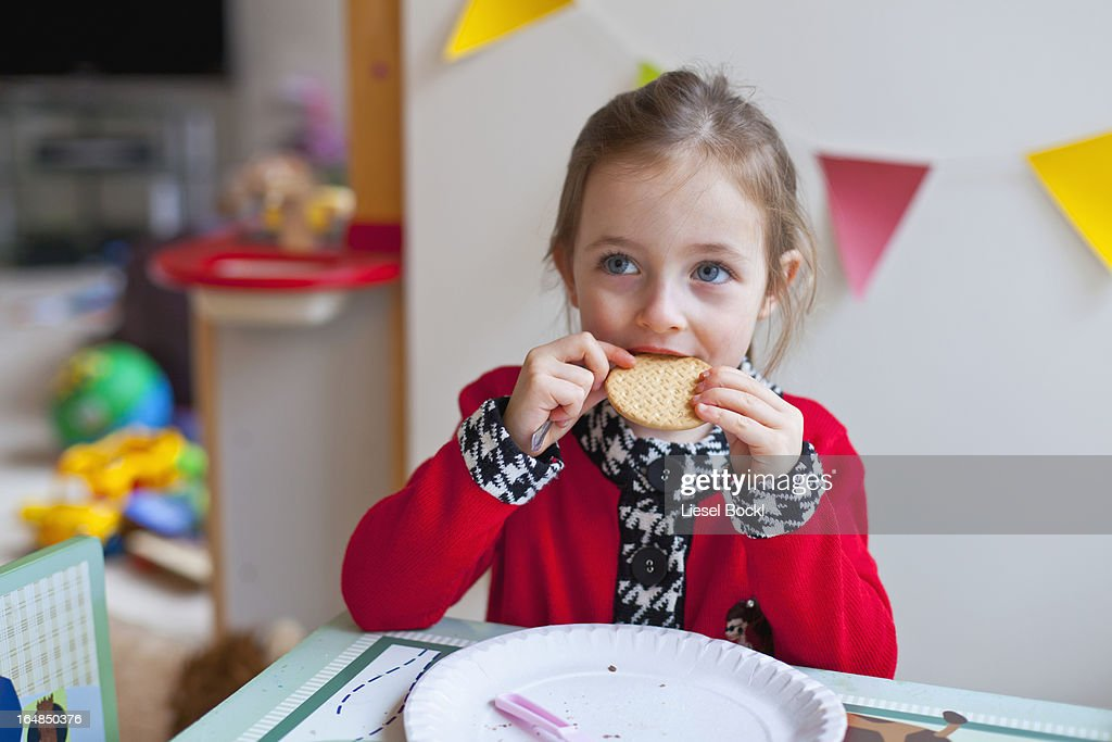 A little girl sitting at a table, taking a bite out of a cookie