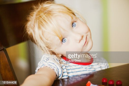 Little girl sitting at dining table : Foto de stock