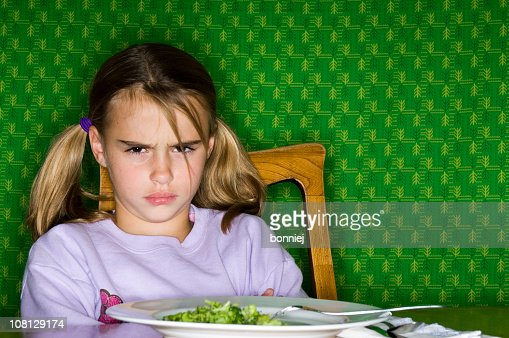Little Girl Sitting at Dinner Table with Plate of Broccoli : Stock Photo