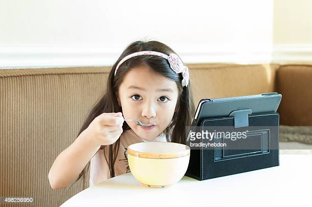 Little girl sitting at kitchen table with iPad eating cereal